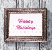 Christmas greeting card with frame on wooden background — Stock Photo