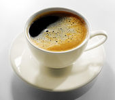 Cup of coffee on grey table — Stock Photo