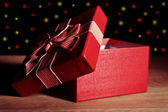 Open gift box on dark background — Stock Photo