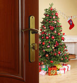 Open door with decorated Christmas tree in room — Stock Photo