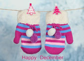 Striped mittens hanging on clothesline as Happy December card — Stock Photo