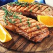 Grilled salmon  and orange slices on cutting board on wooden background — Stock Photo #60866265
