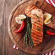 Grilled salmon on cutting board on wooden background — Stock Photo #60866287