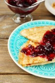 Plate of delicious pancakes with berry jam on plate on wooden background — Stock Photo