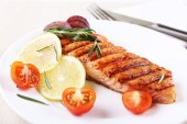 Grilled salmon and vegetables on plate on wooden background — 图库照片