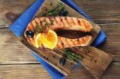 Grilled salmon  and orange slices on cutting board on wooden background — Stock Photo