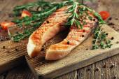 Grilled salmon on cutting board on wooden background — Stock Photo