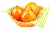 Ripe persimmons in wicker basket isolated on white — Stock Photo