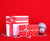 Beautiful bright gifts and Christmas decoration on red background — Stock Photo