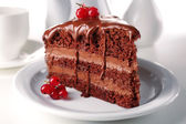 Delicious chocolate cake on plate on table on light background — Stock Photo