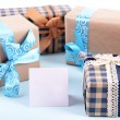 Gift boxes with greeting card on light blue uneven background — Stock Photo #60870767