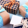 Gift boxes with greeting card on light blue uneven background — Stock Photo #60870775