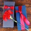 Two gift boxes with red carnation on wooden background — Stock Photo #60872523