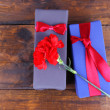 Two gift boxes with red carnation on wooden background — Stock Photo #60872525