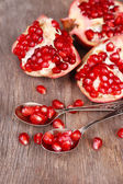 Juicy ripe pomegranates seeds in spoons, on old wooden table — Stock Photo