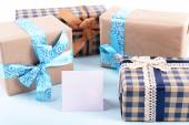 Gift boxes with greeting card on light blue uneven background — Stock Photo