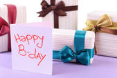 Cute presents with greeting card on light blue uneven surface isolated on white — Stock Photo