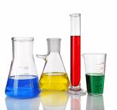 Test-tube and flasks with colorful fluid on light background — Stock Photo