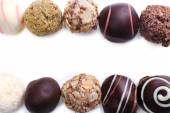 Lines of assorted chocolate candies on a white background — Stock Photo