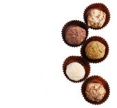 Zigzag of round chocolates wrapped in paper bowl on white background — ストック写真