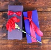 Two gift boxes with red carnation — Stock Photo