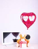 Teddy bear with present box, plant and love heart balloon on wooden  computer table, on the brick wall background — Stock Photo