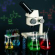 Test tubes with colorful liquids and microscope on dark background — Stock Photo #60926141