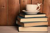 Старые книги и чашка кофе на столе — Стоковое фото