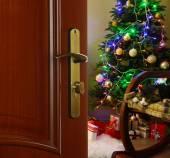 Open door with decorated Christmas tree in room — Stock Photo