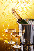 Bottle of champagne in bucket with ice and glasses of champagne, on bright background — Stock Photo
