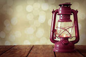 Lantern on wooden table on bright background — Stock Photo