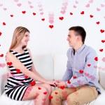 Loving couple sitting on sofa and heart-shaped frame, on light background — Stock Photo #60963053