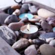 Candles on vintage tray with sea pebbles, on wooden background — Stock Photo #60966927