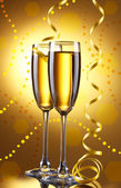 Glasses of champagne with serpentine on bright background — Foto Stock