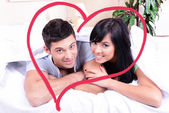 Beautiful loving couple lying in bed and heart-shaped frame — Stock Photo