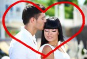 Beautiful young romantic couple and heart-shaped frame — Stock Photo