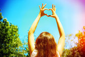 Young woman holding hands in heart shape framing on sky background — Stock Photo