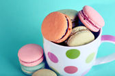 Assortment of gentle colorful macaroons in mug on color background — Stock Photo