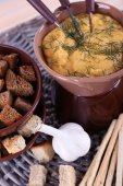 Fondue, bowl of rusks, biscuits, spice and garlic on wicker mat on wooden background — Stock Photo