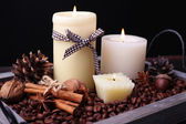 Candles on vintage tray with coffee grains and spices, bumps on wooden table, on dark background — Stock Photo