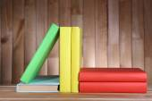 Libros de mesa de madera en el fondo de pared de madera — Foto de Stock