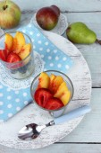 Fresh tasty fruit salad on blue wooden table — Stock Photo