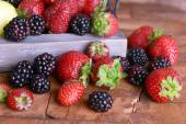 Strawberries and blackberries on tray on wooden background — Stock Photo