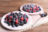 Iced berries on plates, on wooden background — Stock Photo