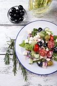 Plate of Greek salad served with olive oil and fresh olives on wooden background — Foto Stock