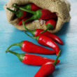 Red hot chili peppers in sack on wooden background — Stock Photo #60971611