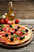 Delicious pizza served on wooden table — Stock Photo