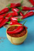 Milled red chili pepper in bowl on wooden background — Stock Photo
