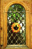 Mooie krans van snoepjes opknoping op oude houten deur — Stockfoto