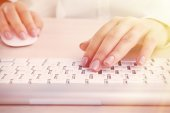 Female hands typing on keyboard on light background — Stock Photo